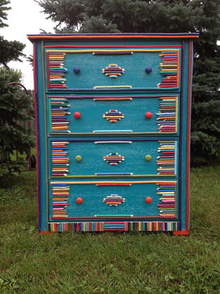 Colorful quirky painted wood dresser with Adirondack stick embellishment painted in a rainbow of colors