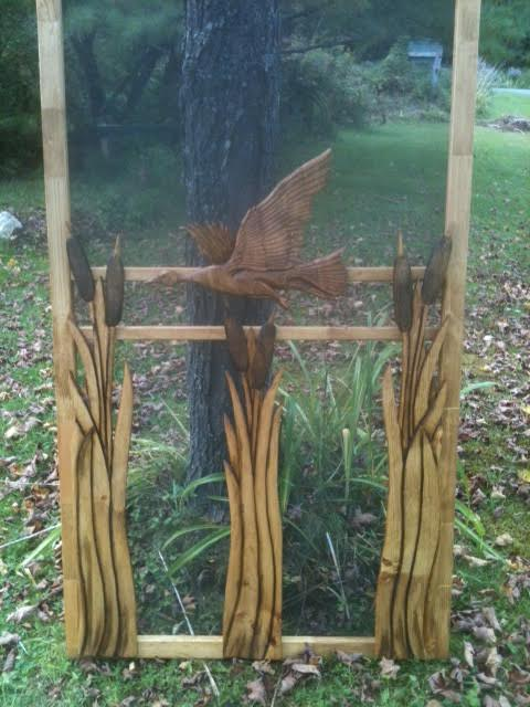 carved wood screen door with cattails and flying duck
