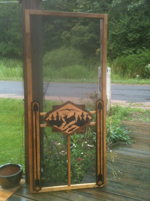 carved wood screen door with leaping buck on center panel