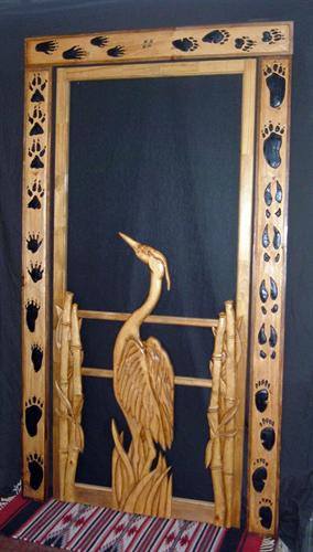 wood screen door with carved loon and paw print door frame