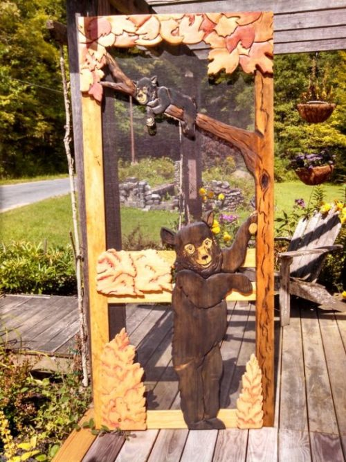 Wood screen door with hand carved bear and cub in a tree