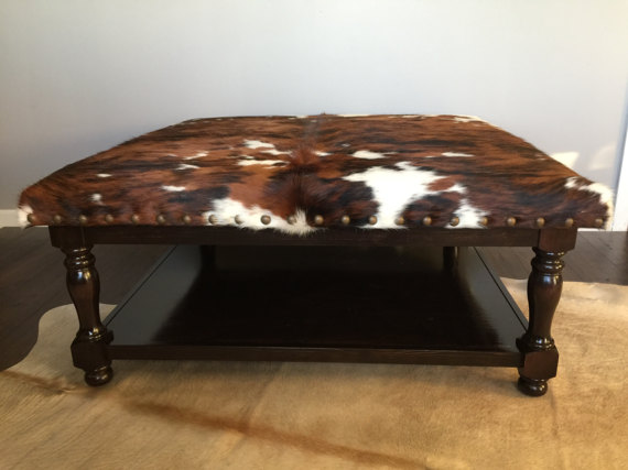 Ottoman Coffee Table With Cowhide Upholstery And Lower Shelf
