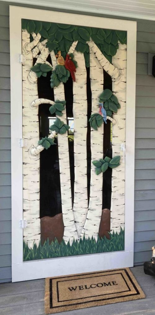 carved screen door with birch trees and birds